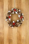 Decorated Christmas Door Wreath Cinnamon, Anise And Pine Cones On Sapele Wood Background