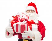 christmas, holidays and people concept - man in costume of santa claus with gift boxes