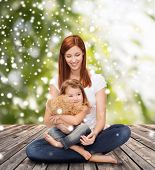 childhood, parenting and people concept - happy mother with little girl and teddy bear toy over wooden floor and green plants background