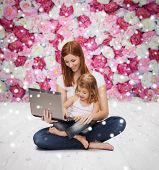 childhood, parenting, people and technology concept - happy mother with little girl with laptop computer over wooden floor and flowers background