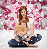 childhood, parenting and people concept - happy mother with little girl and teddy bear toy over wooden floor and flowers background