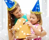 family, childhood, holidays and people concept - happy mother and daughter in blue party hats with gift box