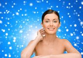 beauty, people and health concept - smiling young woman with bare shoulders over blue snowy background
