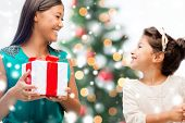 christmas, holidays, family and people concept - happy mother and child girl with gift box at home