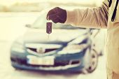 transportation and ownership concept - closeup of man hand with car key outdoors