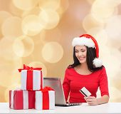 christmas, shopping and people concept - smiling woman in santa helper hat with gift boxes, laptop computer and credit card over beige lights background