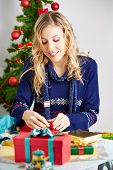 Happy woman wrapping christmas gifts with wrapping paper and ribbon