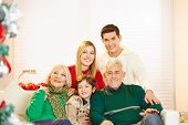 Happy family with child and seniors at christmas sitting at home