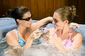 Two Young Women Relaxing In A Jacuzzi poster