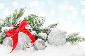 Christmas baubles and red ribbon over snow bokeh background with copy space