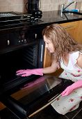 stock photo of house cleaning  - Young woman cleaning the oven in the kitchen - JPG