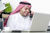 Arabian businessman having a phone conversation in his office