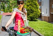 Young sportive woman with groceries in a basket bike