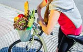 Closeup of woman winth groceries in a basket bike