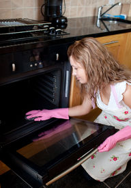 pic of house cleaning  - Young woman cleaning the oven in the kitchen - JPG