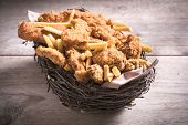 pic of fried chicken  - Wooden basket stuffed with fried chicken and French fries selective focus - JPG