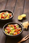 foto of sweet-corn  - Bowls of fresh vegetable salad made of sweet corn cherry tomato cucumber red onion red pepper chives with toasted bread on the side photographed on dark wood with natural light  - JPG
