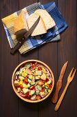 picture of sweet-corn  - Overhead shot of fresh vegetable salad made of sweet corn cherry tomato cucumber red onion red pepper chives with croutons in wooden bowl photographed on dark wood with natural light - JPG