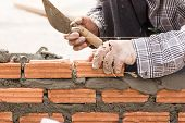 picture of brick block  - Bricklayer working in construction site of a brick wall - JPG