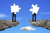 stock photo of comrades  - Businessmen holding two white jigsaw puzzles to connect on the cliff with sky background - JPG