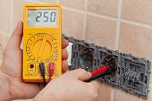stock photo of electrician  - Electrician hands with multimeter measuring the voltage in a partially installed wall fixture  - JPG
