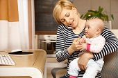 foto of young baby  - Young woman talking on mobile holding baby on lap - JPG
