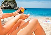 picture of suntanning  - Woman applying suntan lotion from a spray bottle  - JPG