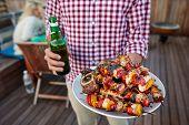 image of kebab  - Man serves skewer kebabs for outdoor barbeque dinner party holding beer - JPG