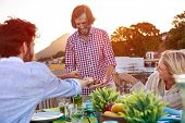 picture of bbq party  - Man serves friends skewer kebabs at outdoor rooftop barbeque dinner party - JPG