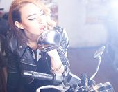 stock photo of chopper  - Attractive young woman driving a shiny chopper - JPG