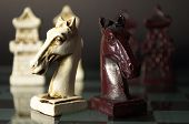 stock photo of humility  - black and white chess horses are located on a glass chessboard - JPG
