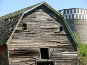 weathered abandoned barn with silo