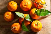 foto of clementine-orange  - Juicy fresh clementines against a wooden background - JPG