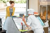stock photo of confectioners  - Confectioner selling ice cream to young woman in the pastry shop - JPG