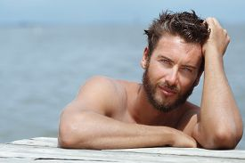 picture of macho man  - Close up Portrait of Smiling Gorgeous Handsome Man with No Shirt Posing at the Sea - JPG