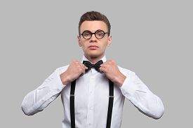 pic of nerds  - Serious young nerd man adjusting his bow tie and looking at camera while standing against grey background - JPG