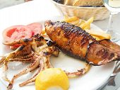 stock photo of squid  - Greek style stuffed squid baked on grill - JPG