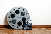 image of mm  - 35 mm cinema movie roll with clapper on wooden floor and white wall background - JPG
