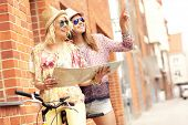 picture of tandem bicycle  - A picture of two girl friends using a map and riding a tandem bicycle in the city - JPG