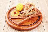 stock photo of cinnamon sticks  - sweet apple cake with lemon and cinnamon sticks on wooden table - JPG