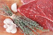 foto of flesh  - fresh raw beef meat fillet flesh with peppercorn and thyme ready to grill on wood figured old style board isolated over white background - JPG