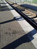 pic of train track  - Long shadows over a light rail train track - JPG