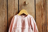 pic of habilis  - Child dress on hanger on wooden wall background - JPG