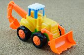 stock photo of backhoe  - Vintage Style Tractor Backhoe Toy on sand - JPG