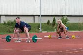 picture of bent over  - A Group Of Young People In Aerobics Class Doing A Bent Over Barbell Row Exercise Outdoor - JPG