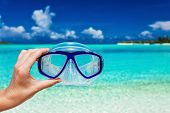stock photo of sky diving  - Hand holding snorkel googles against blurred beach and blue sky - JPG