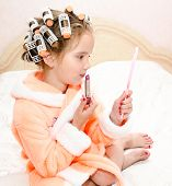 picture of hair curlers  - Cute little girl with lipstick and mirror and hair curlers - JPG