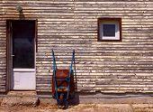 image of wheelbarrow  - Rusty old wheelbarrow leaning against wall  - JPG