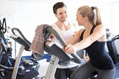 image of elliptical  - Handsome Young Fitness Trainer Explaining Something to a Young Woman While on Elliptical Bike Device Inside the Gym - JPG