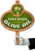 stock photo of virgin  - Hand of chef holding a wooden sign with green olives and oil text Extra virgin olive - JPG
